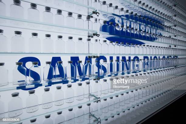 Samsung BioLogics Co. Signage is seen behind medicine bottles on display at the company's headquarters and production facilities in Songdo district...