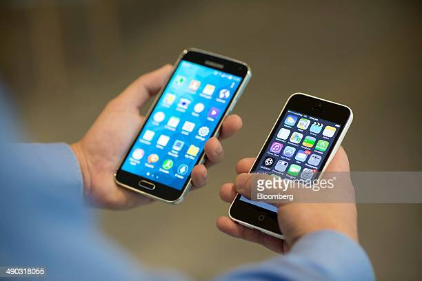 A Samsung Electronics Co Galaxy S5 smartphone left and Apple Inc iPhone 5c are held for a photograph in Hong Kong China on Wednesday May 14 2014...