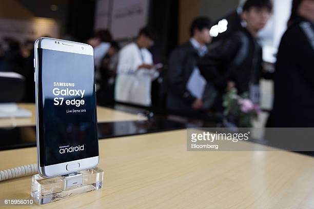 A Samsung Electronics Co Galaxy S7 Edge smartphone stands on display as customers wait in line during the release of the Apple Inc iPhone 7 at KT...