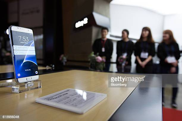 A Samsung Electronics Co Galaxy S7 Edge smartphone stands on display as employees wait to greet customers during the release of the Apple Inc iPhone...