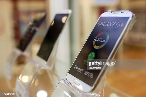 Samsung Electronics Co. Ltd. Galaxy S4 smartphone, right, sits on display inside an OAO Mobile TeleSystems retail outlet in Moscow, Russia, on...