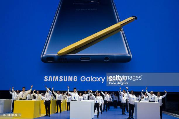 Samsung employees wave as they introduce the new Samsung Galaxy Note 9 smartphone at the Barclays Center August 9 2018 in the Brooklyn borough of New...