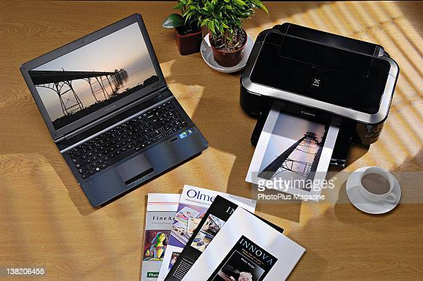 A Samsung laptop computer and a Canon printer alongside a selection of photo paper taken on June 1 2011
