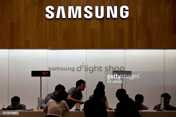 A Samsung logo is displayed above a checkout counter at a Samsung showroom in Seoul on July 31 2014 Samsung Electronics reported a near 20 percent...
