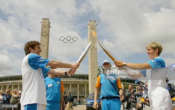 Samsung torchbearer Andreas Franke receives the Olympic Flame from Rosemarie Ackermann at the launch site outside the Olympic Stadium during the...