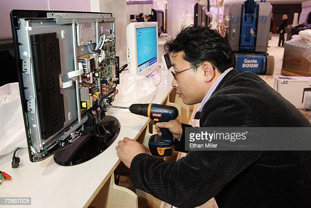 Samsung's DP Choi puts together one of the company's flat panel televisions at the Las Vegas Convention Center as preparations continue for the...