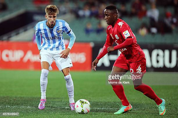 Samu Castillejo of Malaga competes for the ball with Mark Ochieng of Adelaide during the international club friendly match between Adelaide United...