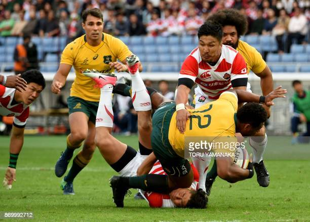 TOPSHOT Samu Kerevi of Australia is tackled during the rugby union test match between Japan and Australia in Yokohama suburb of Tokyo on November 4...