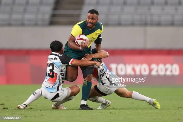 Samu Kerevi of Team Australia takes on Gwong Min Kim and Hyunsoo Kim of Team South Korea during the Men's Pool A Rugby Sevens match between Australia...