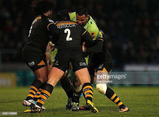Samu Manoa of Northampton is tacked by Ashley Johnson and Carlo Festuccia of Wasps during the Aviva Premiership match between London Wasps and...