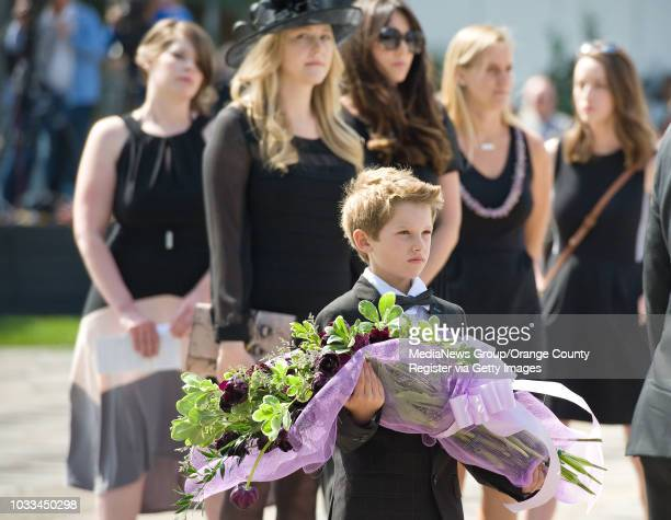 Samual Milner, the youngest grandson of of Crystal Cathedral founder Robert H. Schuller, carries tulips as he follows the casket procession Monday at...