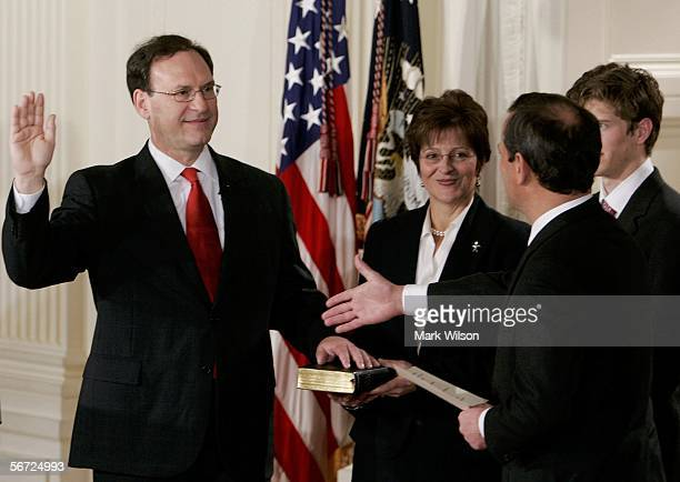 Samuel Alito is sworn in as Associate Justice of the United States Supreme Court while Chief Justice John Roberts reaches for a handshake while...