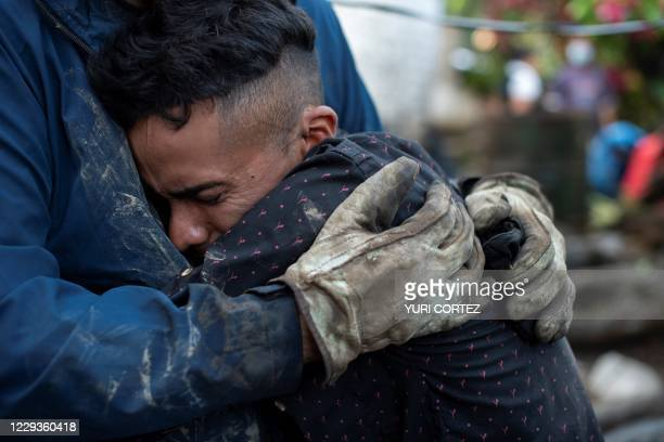 Samuel Amilcal Erroa who survived a landslide, but his mother and a brother, is comforted by a government official amid the rubble of his home in...