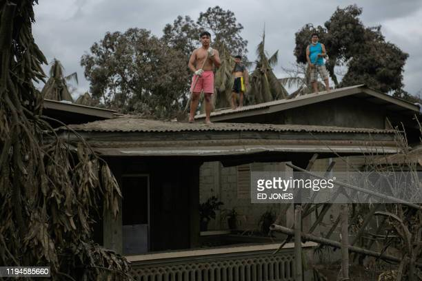 Samuel Atul poses for a portrait as he works to clear volcanic ash from the eruption of the Taal volcano from the roof of his house in Buso Buso on...