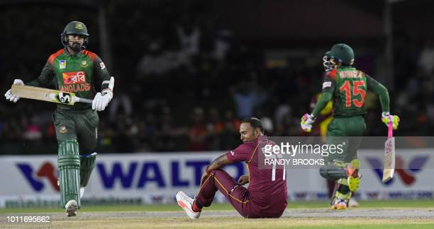 Samuel Badree of West Indies fell as Liton Das and Mushfiqur Rahim of Bangladesh run during the 3rd and final T20i match between West Indies and...