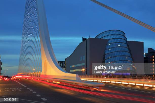 samuel beckett bridge and convention centre at dusk with light trails of passing traffic - rainer grosskopf stock pictures, royalty-free photos & images