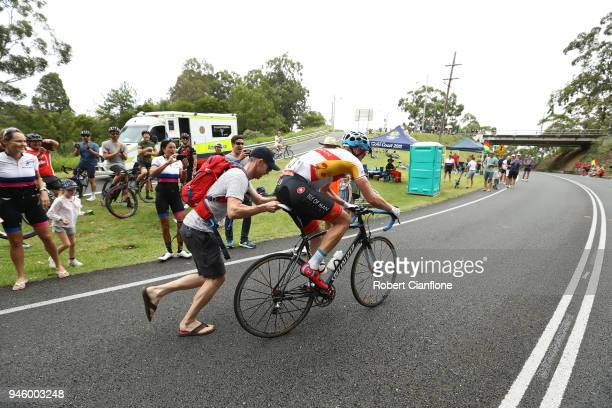 Samuel Brand of the Isle of Man borrows a bike from a spectator after breaking a rear derailleur on his own bike during the Men's Road Race on day 10...