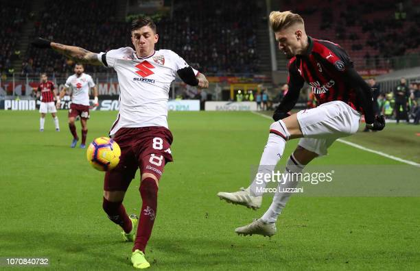 Samuel Castillejo of AC Milan is challenged by Daniele Baselli of Torino FC during the Serie A match between AC Milan and Torino FC at Stadio...