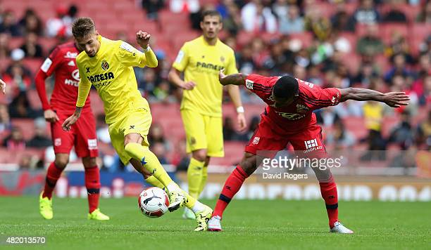 Samuel Castillejo of Villarreal is tackled by Claudio Beauvue during the Emirates Cup match between Olympique Lyonnais and Villarreal at the Emirates...