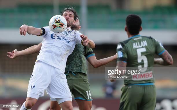 Samuel Di Carmine of Hellas Verona jumps for the ball against Nikola Maksimovic of SSC Napoli during the Serie A match between Hellas Verona and SSC...