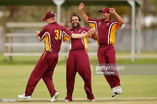 Samuel Doggett Preston White and Worrin Williams of Queensland celebrate a wicket during the Imparja Cup match between Queensland and the Northern...