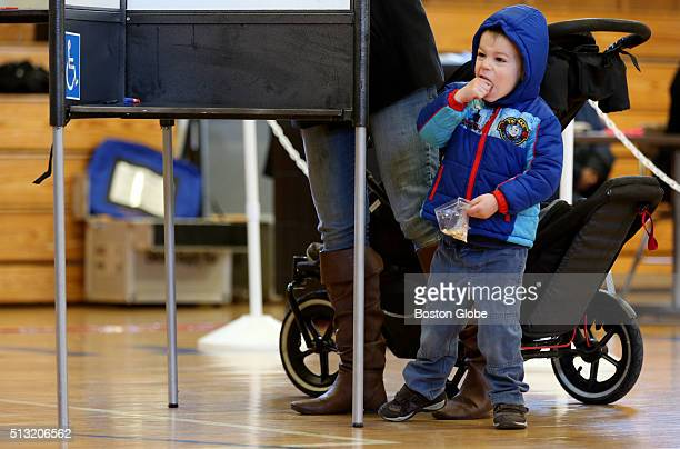 Samuel Douthit occupies himself with animal crackers while his mother Kristen fills out her ballot at East Boston High School during the...