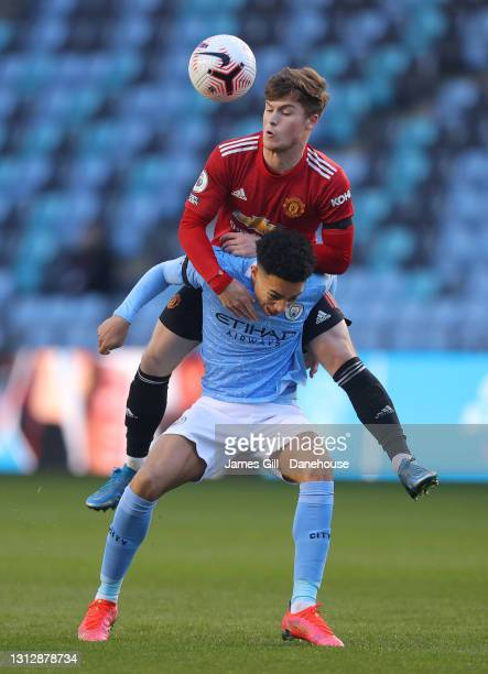Samuel Edozie of Manchester City is challenged by Charlie McCann of Manchester United during the Premier League 2 match between Manchester City and...