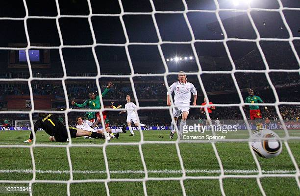 Samuel Eto'o of Cameroon scores past Thomas Sorensen of Denmark during the 2010 FIFA World Cup South Africa Group E match between Cameroon and...