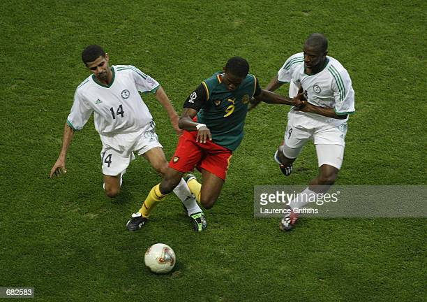 Samuel Eto'o of Cameroon takes the ball past Abdulaziz al Khathran and Abdullah Sulaiman Zubromawi of Saudi Arabia during the FIFA World Cup Finals...