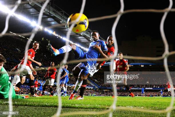 Samuel Eto'o of Chelsea scores his team's third goal and completes his hat trick despite the challenge from Antonio Valencia of Manchester United...
