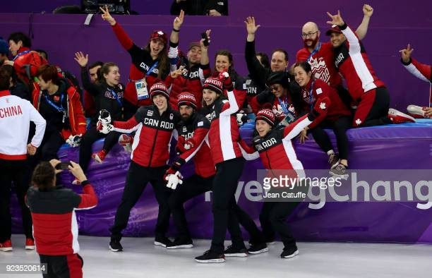 Samuel Girard Charles Hamelin Charle Cournoyer and Pascal Dion of Canada celebrate their third place with staff following the Short Track Speed...