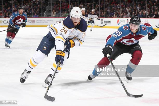 Samuel Girard of the Colorado Avalanche defends against Hudson Fasching of the Buffalo Sabres at the Pepsi Center on December 5 2017 in Denver...