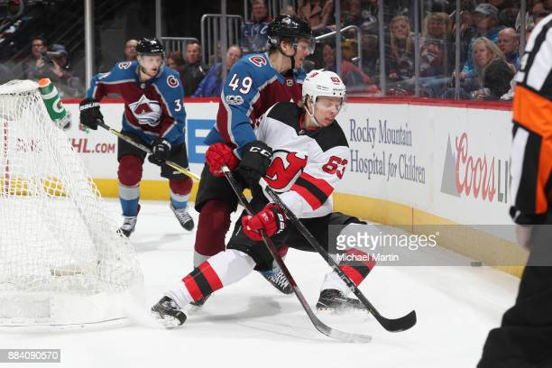Samuel Girard of the Colorado Avalanche fights for positon against Jesper Bratt of the New Jersey Devils at the Pepsi Center on December 1 2017 in...