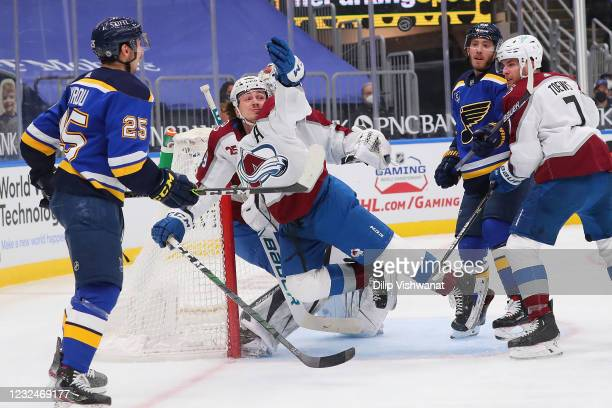 Samuel Girard of the Colorado Avalanche knocks the puck pout the air as Mike Hoffman of the St. Louis Blues and Devon Toews of the Colorado Avalanche...