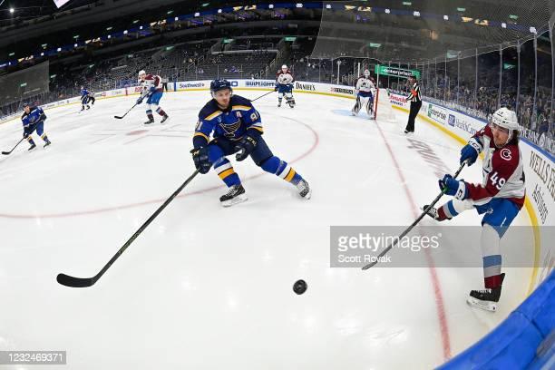 Samuel Girard of the Colorado Avalanche makes a pass as Vladimir Tarasenko of the St. Louis Blues defends on April 22, 2021 at the Enterprise Center...