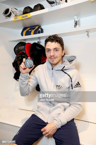 Samuel Girard of the Nashville Predators holds the puck from his first career NHL goal scored during an NHL game against the Dallas Stars at...