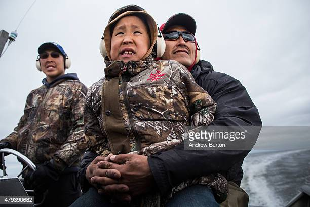 Samuel John age 8 is his held by his dad Joseph John Jr while his brother Jeremiah John steers the boat to go salmon fishing on July 1 2015 in Newtok...
