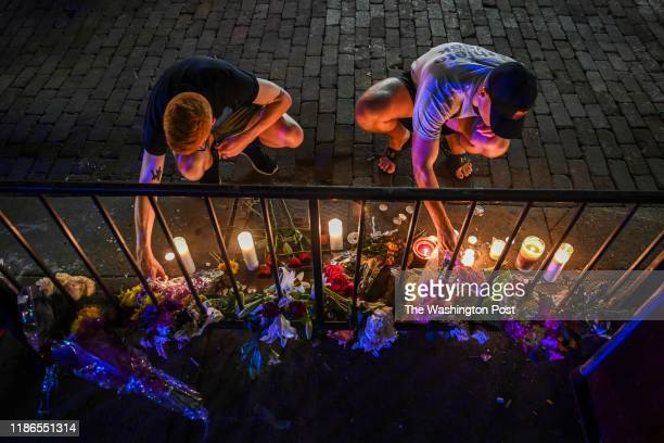 Samuel Klug L and John Neff place candles around a makeshift memorial at the scene of a mass shooting in the city's historic Oregon District where...