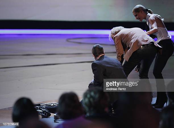 Samuel Koch receives first aid after he falls down the floor after he jumped over a car during the 192th 'Wetten dass ' show at the exhibition hall...
