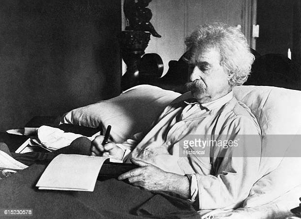 Samuel Langhorne Clemens lies in his bed and writes