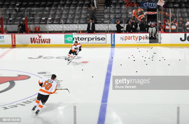 Samuel Morin and Mike Vecchione of the Philadelphia Flyers skate out for warmups as the remaining Flyers wait in the tunnel prior to playing in their...