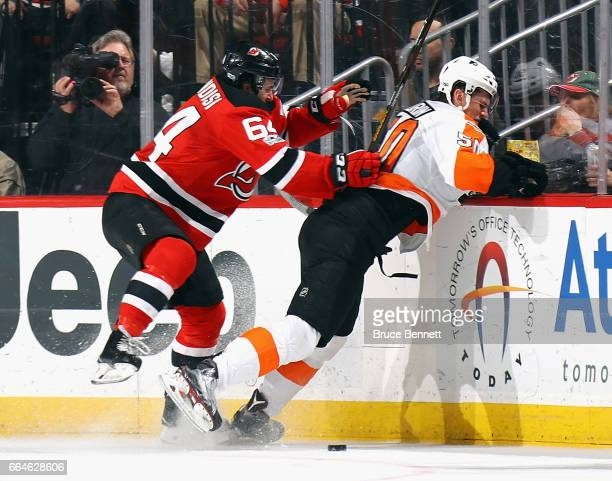 Samuel Morin of the Philadelphia Flyers is hit into the boards by Joseph Blandisi of the New Jersey Devils during the first period at the Prudential...