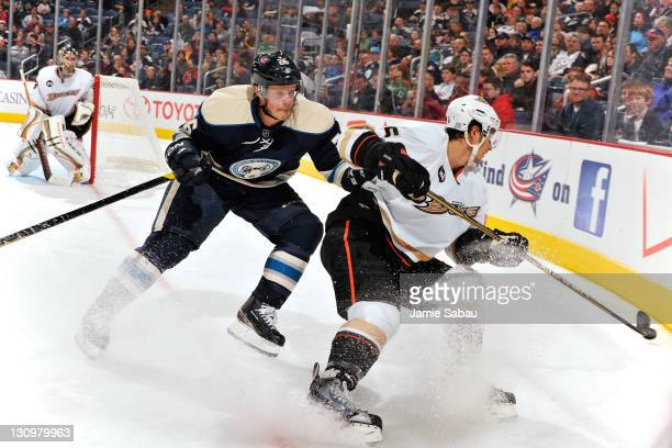 Samuel Pahlsson of the Columbus Blue Jackets and Luca Sbisa of the Anaheim Ducks battle for control of a loose puck during the third period on...