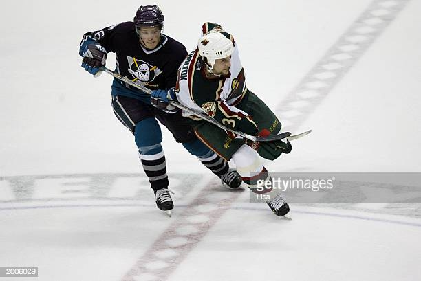 Samuel Pahlsson of the Mighty Ducks of Anaheim hooks Sergei Zholtok of the Minnesota Wild in game one of the 2003 Western Conference Finals of the...