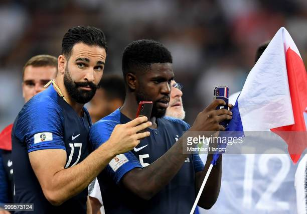 Samuel Umtiti and Adil Rami of France take a photo following the 2018 FIFA World Cup Final between France and Croatia at Luzhniki Stadium on July 15...