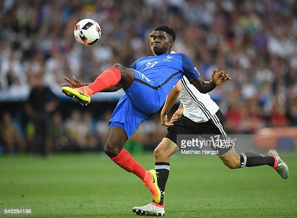 Samuel Umtiti of France clears the ball under pressure from Thomas Mueller of Germany during the UEFA EURO semi final match between Germany and...