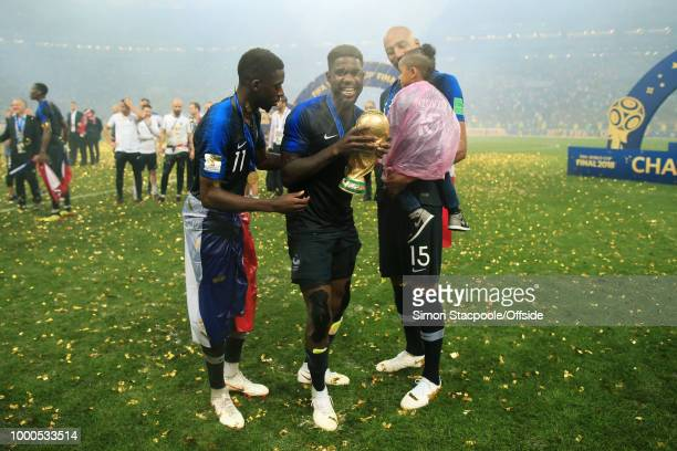 Samuel Umtiti of France holds the trophy alongside Ousmane Dembele of France and Steven N'Zonzi of France after the 2018 FIFA World Cup Russia Final...