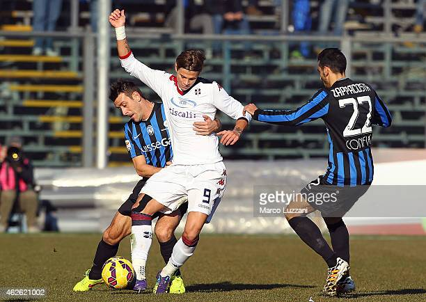 Samuele Longo of Cagliari Calcio competes for the ball with Gianpaolo Bellini and Davide Zappacosta of Atalanta BC during the Serie A match between...