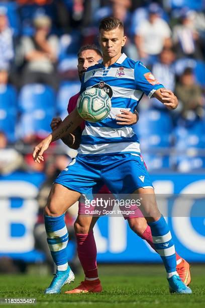Samuele Longo of Deportivo de La Coruna is challenged by Miguel Cifuentes of Malaga CF during the La Liga Smartbank match between Deportivo de La...