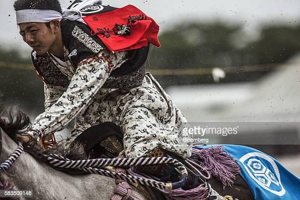 Samurai horseman competes in the Kachu Keiba race during the Soma Nomaoi festival at Hibarigahara field in Minamisoma, Fukushima Prefecture, Japan,...